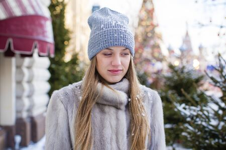 Portrait of a young woman in a blue knitted hat and gray mink coat, posing in the street in winter Stock Photo
