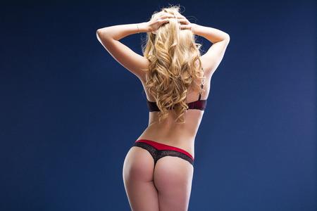 Hintere Ansicht, junge Blondine, die im schwarzen Bikini über dunkelblauem Hintergrund aufwerfen