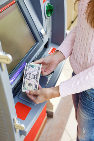 withdrawing: Repayment on credit. Woman hand withdrawing money from outdoor bank ATM Stock Photo