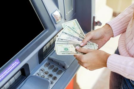 Terugbetaling op krediet. Vrouwenhand die geld van openluchtbank ATM terugtrekken Stockfoto