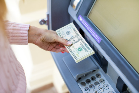 Repayment on credit. Woman hand withdrawing money from outdoor bank ATM Stock Photo