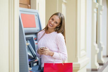 automatic transaction machine: hermosa joven rubia con un teléfono está en el fondo en el centro comercial ATM Foto de archivo