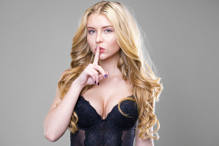 Woman requires silence. Young beautiful blonde girl has put forefinger to lips as sign of silence, isolated on gray background