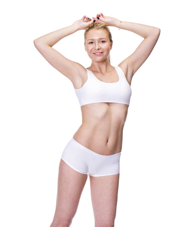 Young beautiful blonde woman in white fitness clothing, isolated on white background Stock Photo