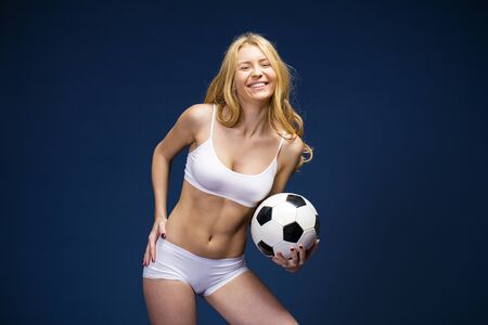 Happy girl holding a soccer ball. Young beautiful blonde woman in white fitness clothing, dark blue isolated background