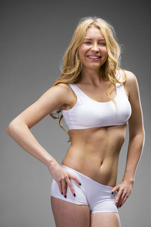 sexy blonde girl: Young beautiful blonde woman in white fitness clothing, dark gray isolated background