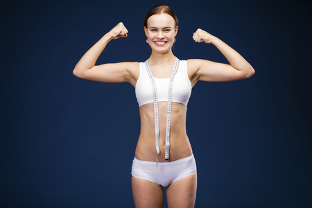 La forza di una donna nella sua debolezza. La perdita di peso e il concetto di assistenza sanitaria. Forte bella ragazza bruna in abbigliamento fitness bianco