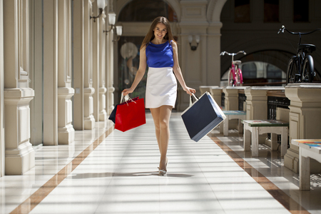 go shopping: Young beautiful brunette woman with some shopping bags in the mall