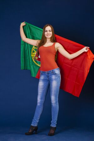 drapeau portugal: Young beautiful woman holding a large flag of Portugal, dark blue studio background