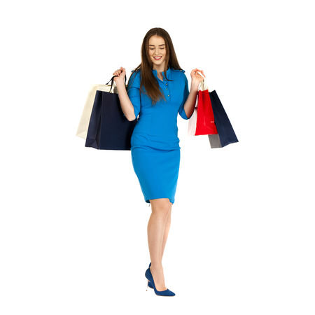 Fashion woman portrait isolated. White background. Happy girl hold shopping bags. Blue dress. female beautiful model
