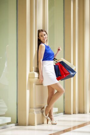 full height: Young beautiful brunette woman with some shopping bags in the mall