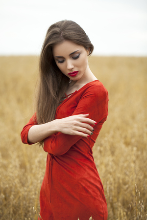 Portrait of a young brunette woman in red dress on a background of golden oats field, summer outdoors Stock Photo
