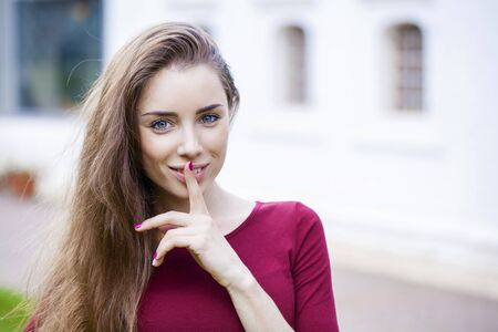Young beautiful brunette woman has put forefinger to lips as sign of silence, against white wall Stock Photo