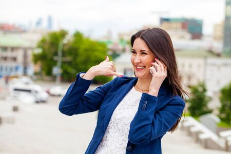 call me: Beautiful brunette woman making a call me gesture, summer outdoors