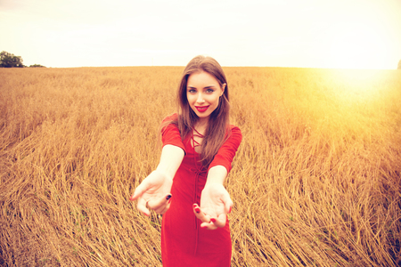 Follow me, Young beautiful brunette woman pulls the arm of her boyfriend in the oats field Stock Photo