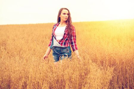 Young beautiful brunette woman in blue jeans short walking in a field, summer outdoors Stock Photo