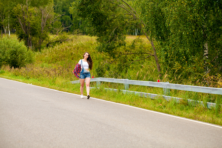Young beautiful brown haired woman in blue jeans short walking on the road