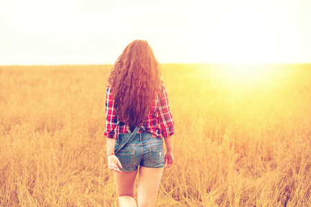 Portrait of a young brunette woman in a red plaid shirt on a background of golden oats field, summer outdoors
