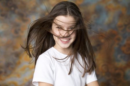 Hair Style Wind. Portrait of a charming little girl on studio wall background