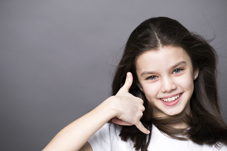 Sign Call me. Pretty brunette litte girl, isolated on gray background Stock Photo