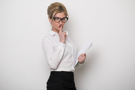 Young secretary requires silence. Young beautiful blonde woman has put forefinger to lips as sign of silence, on white wall background Stock Photo