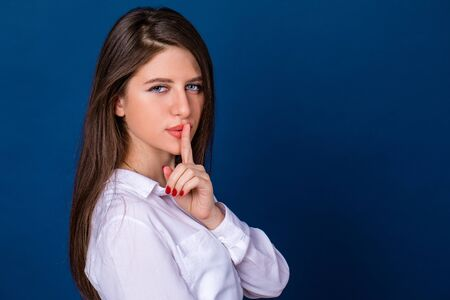 forefinger: Young beautiful brunette woman has put forefinger to lips as sign of silence, against blue wall Stock Photo