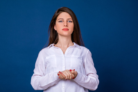 Happy brunette woman in white shirt, isolated on blue background