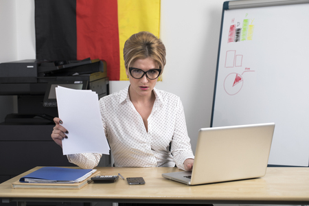 German secretary at work. Portrait of a young blonde business woman at office Standard-Bild