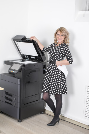 fotocopiadora: Young beautiful woman in a black polka-dot dress making copies in the office