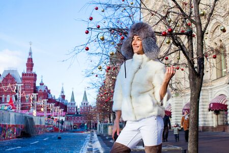 visone: Portrait of a Young beautiful woman in white short mink coat, posing in winter Red Square in central Moscow