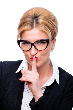 Young secretary requires silence. Young beautiful blonde woman has put forefinger to lips as sign of silence, on white wall background Banco de Imagens
