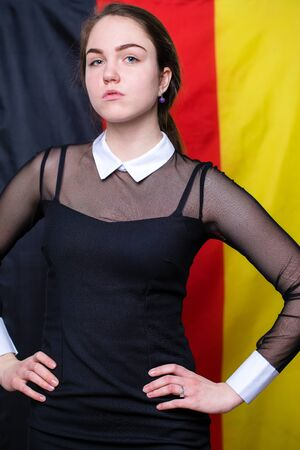 Portrait of a beautiful calm brunette girl in the background of the German flag Stock Photo