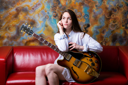 Young beautiful girl sitting on a red couch with electric guitar