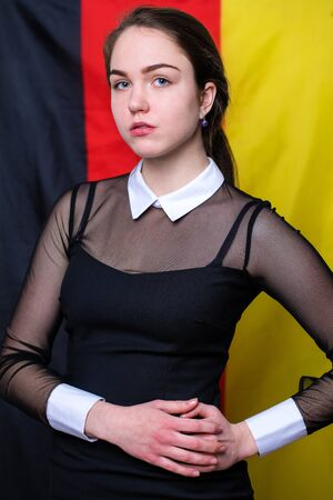 16s: Portrait of a beautiful calm brunette girl in the background of the German flag Stock Photo