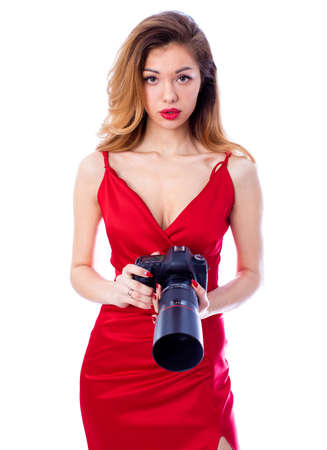 Happy blonde photographer woman in sexy red dress holding camera, isolated on white background Stock Photo
