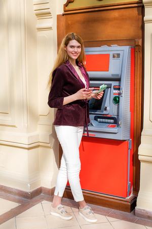 automatic transaction machine: Joven y bella mujer rubia con un teléfono y el dinero está en el fondo en el centro comercial ATM