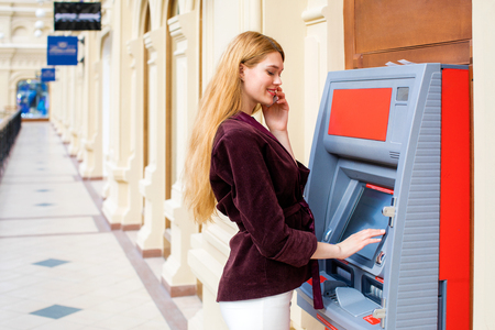 automatic transaction machine: Young beautiful blonde woman with a phone is on the background in shopping center ATM