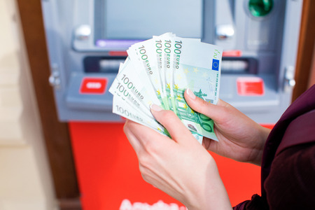 automatic transaction machine: A bundle of money from one hundred euros. Womens hands hold money denominations of 100 euros. Cash out money at an ATM Foto de archivo
