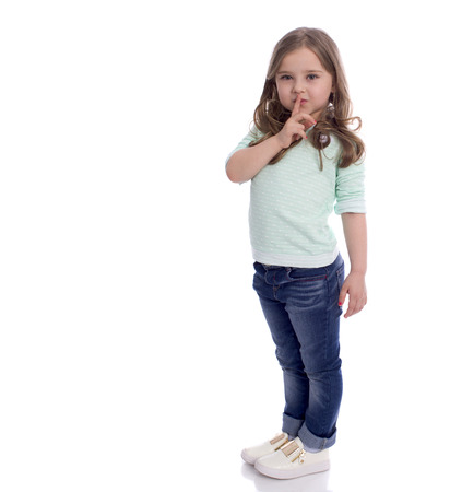 Little girl requires silence. Young beautiful kid has put forefinger to lips as sign of silence, isolated on white background Stock Photo