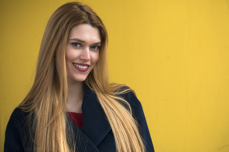 Portrait of a young beautiful woman in blue coat, Happy blonde model against the yellow wall