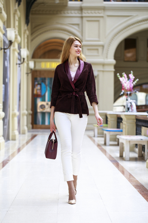 go shopping: Young beautiful blonde woman in a corduroy jacket walking in a shopping center