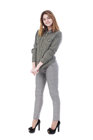 19's: Young beautiful blonde girl in gray trousers and green shirt, isolated on white background
