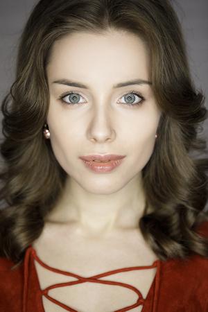 Primer plano retrato de una mujer joven. Hermosa morena ardiente en fondo oscuro pared del estudio