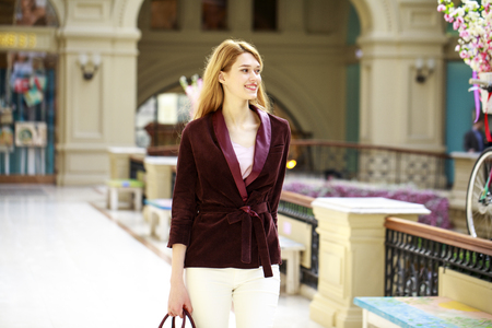 Young beautiful blonde woman in a corduroy jacket walking in a shopping center
