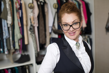 checkroom: Close up portrait of red hair woman. Stylist for clothes in showroom Stock Photo