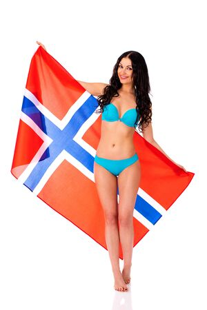 Young beautiful brunette woman in blue bikini holding a large transparent flag of Norway, isolated on white background