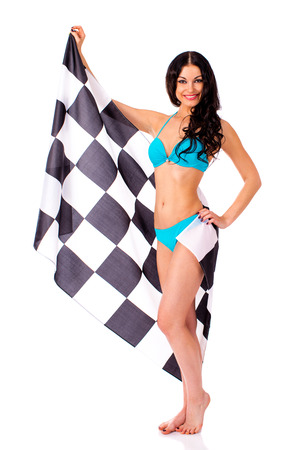 Young beautiful brunette woman in blue bikini holding a large checkered flag, isolated on white background
