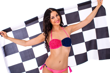 Young beautiful brunette woman in bikini holding a large checkered flag, isolated on white background Stock Photo