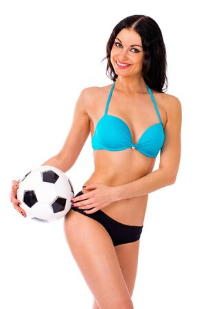 Cheerleader, with a soccer ball, young sexy brunette woman in bikini, isolated on white background