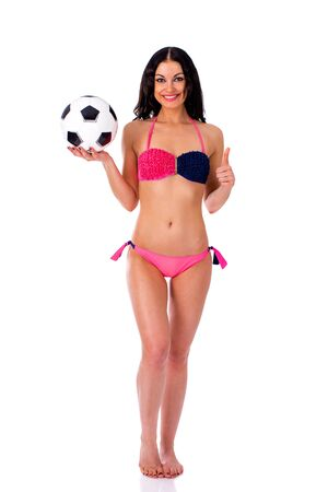 porrista: Young beautiful cheerleader with soccer ball. Full length beautiful slim tanned woman in bikini, isolated on white background Foto de archivo